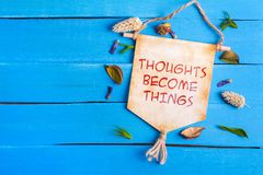 Thoughts become things text on Paper Scroll. With dried flower around and blue wooden background royalty free stock image
