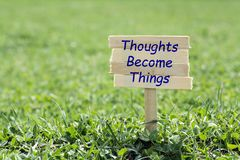 Thoughts become things. Wooden sign in grass,blur background royalty free stock images