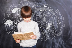Thoughts of boy against the black chalkboards Royalty Free Stock Images