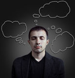 Thoughts in the clouds. Portrait of a young man with empty speech clouds over his head Royalty Free Stock Images