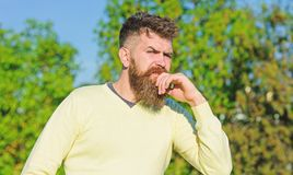 Thoughts concept. Bearded man have rest on sunny day outdoors. Man with beard and mustache on thoughtful face at balcony. Trees on background, defocused. Man royalty free stock photography