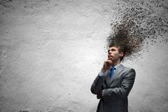 Thoughts in head. Young thoughtful businessman and thoughts above his head Royalty Free Stock Photo
