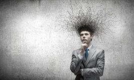 Thoughts in head. Young thoughtful businessman and thoughts above his head Royalty Free Stock Photos