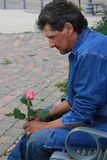 Thoughts of Love. Handsome man sitting on a park bench holding a pink rose bud Royalty Free Stock Images
