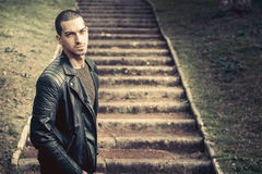 Thoughts, male anxiety. Model handsome man near steps. A handsome young man model outdoors. Near the steps in a park. He wears a leather jacket. Short hair Stock Photography