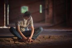 Durchdachter Mann, der im Gebäude sitzt Lizenzfreies Stockfoto