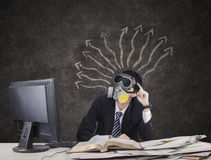 Thougtful Businessman wearing gas mask. With arrows on blackboard Royalty Free Stock Photography
