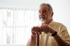 Thougtful senior man looking away while holding walking cane Royalty Free Stock Photos