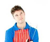 Thougtful young cook holding a cookware Royalty Free Stock Images