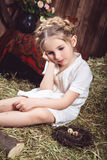 Thougthful little girl sitting on hay Stock Images