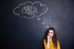 Thougthful woman thinking about problems over blackboard background Royalty Free Stock Image