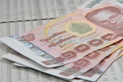 Thousand baht notes on stock quotes. A couple of Thai 1000 baht notes on stock quotes sheet stock photo