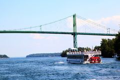 Thousand Islands International Bridge Over Saint Lawrence River. A cruise boat approaches the Thousand Islands International Bridge on the St. Lawrence River stock image