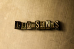 THOUSANDS - close-up of grungy vintage typeset word on metal backdrop Stock Photos