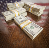 Thousands of Dollars with Reflection of American Flag on Table Royalty Free Stock Photo