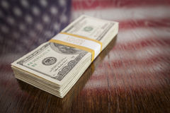 Thousands of Dollars with Reflection of American Flag on Table. Thousands of Dollars Stacked with Reflection of American Flag on Wooden Table stock photography