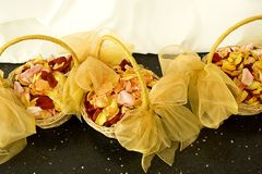 Thousands of Fresh Rose Petals. Three baskets with satin bows and filled with fresh rose Petals on Marble floor at Wedding Reception Stock Photography