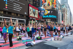 Thousands of New Yorkers practicing yoga in Times Square. Stock Photos