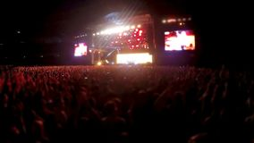 Thousands people standing in front of stage and clapping, rock band concert