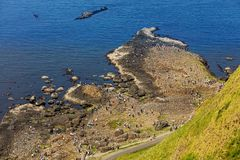 Thousands of tourists visiting Giant`s Causeway in County Antrim of Northern Ireland. A World Heritage Site by UNESCO containing about 40000 interlocking royalty free stock image