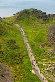 Thousands of tourists visiting Giant`s Causeway in County Antrim of Northern Ireland. A World Heritage Site by UNESCO containing about 40000 interlocking stock images