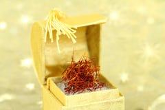 Thrads de safran dans une boîte d'or Image stock