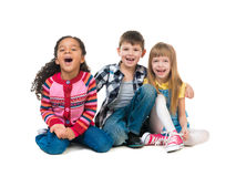Thre cheerful kids sitting on the floor in a studio Stock Photo