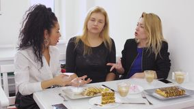 Young girls quarrels in cafe. Thre girls are relaxing in modern cafe and talking. Curly brunette quarrels with her girlfriends. Two women tries to discuss the stock footage