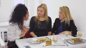 Three girlfriends quarrels in cafe, one of them goes away. Thre girls are relaxing in modern cafe and talking. Curly brunette quarrels with her girlfriends. Two stock video