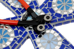 Thre mosaic craft tile nipper for mosaics. Mosaic craft tile nipper/cutter with red handles and two wheels for cutting mosaics in half on a cross Royalty Free Stock Photography