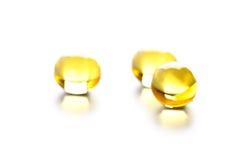 Thre yellow gelatin pills. On white background Royalty Free Stock Image
