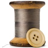 Thread. Spool of thread and a button on white Stock Image