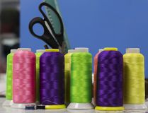 The thread of acidic flowers in the bobbins stand on a blue background.  royalty free stock photos