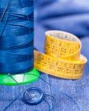 Thread bobbin, button, measure tape on blue dress Royalty Free Stock Photos