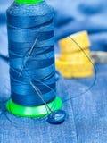 Thread bobbin, button, measure tape on blue fabric Stock Photo