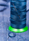 Thread bobbin with needle, button on blue cloth Royalty Free Stock Photography