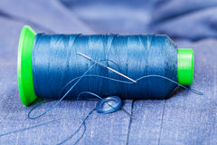Thread bobbin with needle, button on blue jacket Stock Image