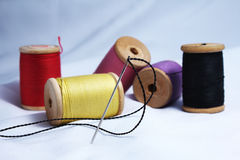 Thread bobbins and needle Stock Photography