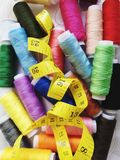 Colored threads with a yellow measuring tape. Thread colorful colours sewinh sewing pins colored threads yellow measuring tape royalty free stock images