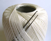 Thread and crochets. Thin crocheting hooks and a spool of cotton thread Royalty Free Stock Photos