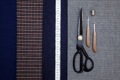 Thread fabric wool sewing man cage blue choice design atelier tailor many different things color tape-measure scissors. Many different in color threads lie on stock photography