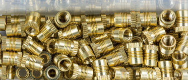 Threaded inserts close-up with mirroring in box. Decorative glossy thread bushings. Pile of small metallic fasteners in golden color. Idea of construction, build stock image