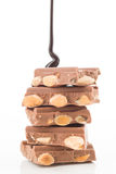 Thread of liquid chocolate, falling tower of pieces of chocolate Stock Photos