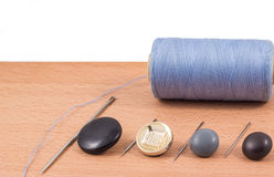 Thread a needle and buttons. Accessories for the textile industry with a needle and thread to sew buttons stock images