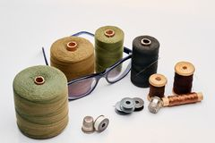 Thread, needle, and glasses. Finely-stranded material in coils, sleeves, rods, reels and kufteh with thimble Stock Photo