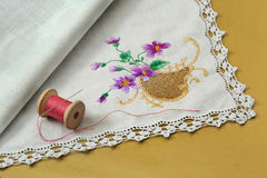 Thread with a needle and a handkerchief on a yellow background Stock Photo
