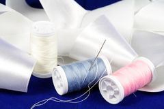 Thread with needle and ribbon. Three reels of thread and needle and white ribbon Royalty Free Stock Photos