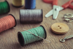 Thread with needle and scissors on wooden table, Vintage tone Royalty Free Stock Photos