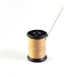 Spool of brown thread and needle Stock Image