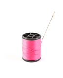 Spool of pink thread and needle Stock Photo